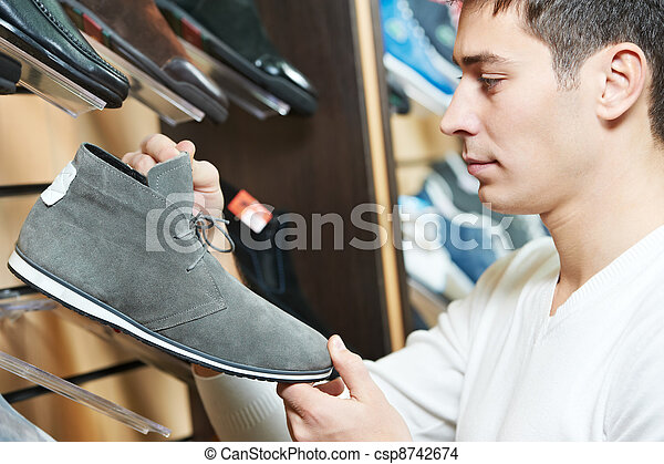 Young man choosing shoe in clothes store - csp8742674