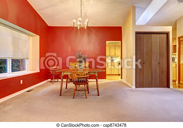 Large dining room with red wall and small wood table. - csp8743478
