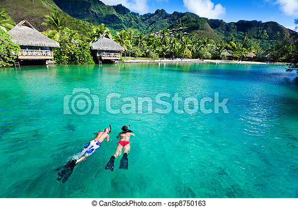 Young couple snorkeling in clean water over coral - csp8750163