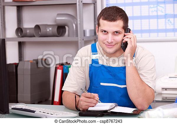 Plumbers' merchant taking a phone call - csp8767243
