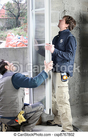 Two men installing new windows - csp8767802