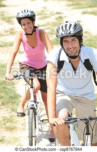 Couple cycling in the countryside - csp8767944