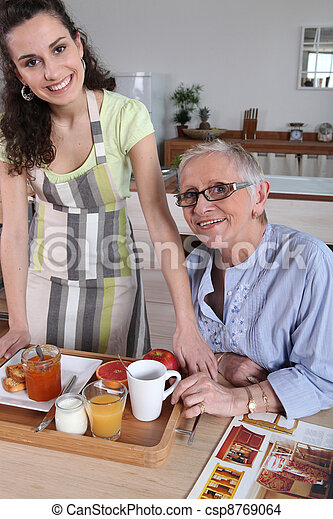 Senior woman being served breakfast at home - csp8769064