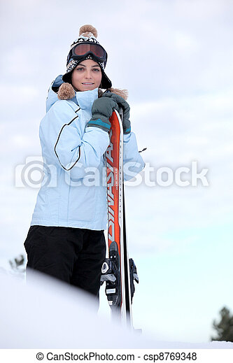 Woman stood on mountain top with skis