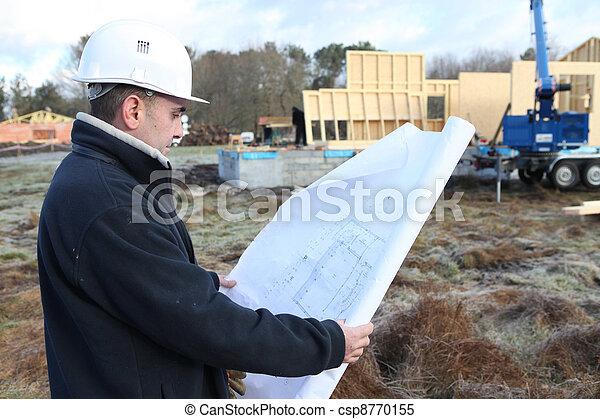 Construction worker examining a blueprint - csp8770155