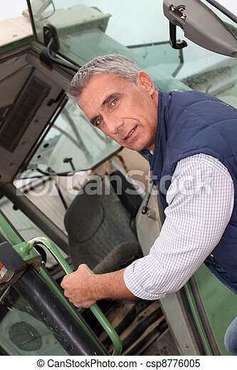 portrait of a farmer climbing on tractor - csp8776005