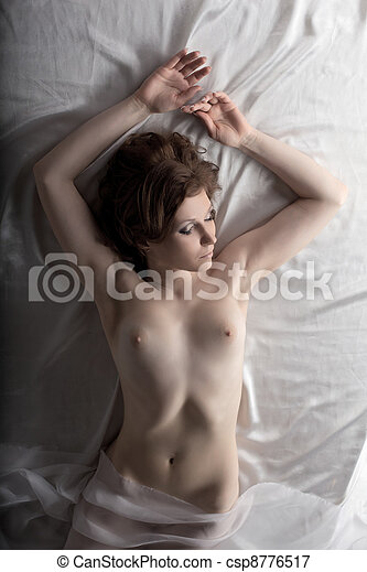 Nude young woman lay on white silk bed - csp8776517