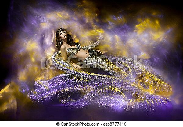 Beautiful woman in fantasy dress. Snake fashion dress stylish - csp8777410