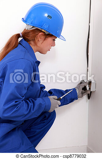 Young female trades apprentice wiring a power point - csp8779032
