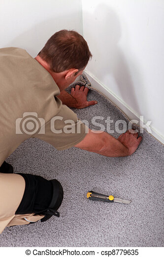 Man fitting carpet into the corner of a room - csp8779635