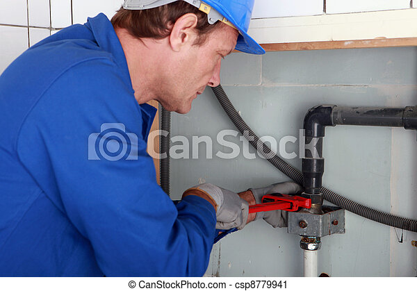 Plumber tightening a joint with a wrench - csp8779941