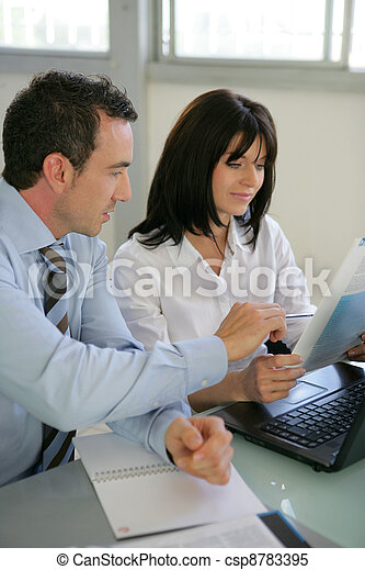 Businesspeople reviewing paperwork - csp8783395