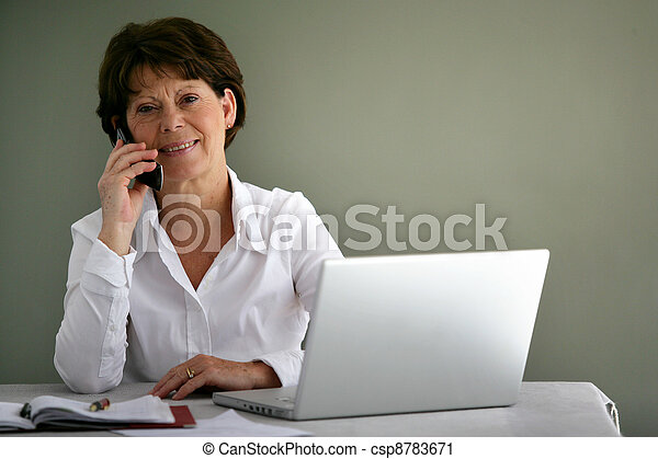 Middle-aged office worker at her desk - csp8783671