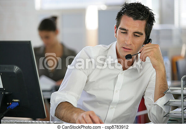 Young man telemarketer in call center - csp8783912