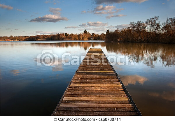 Beautiful image of sunset landscape of wooden fishing jetty on calm lake with clear reflections - csp8788714