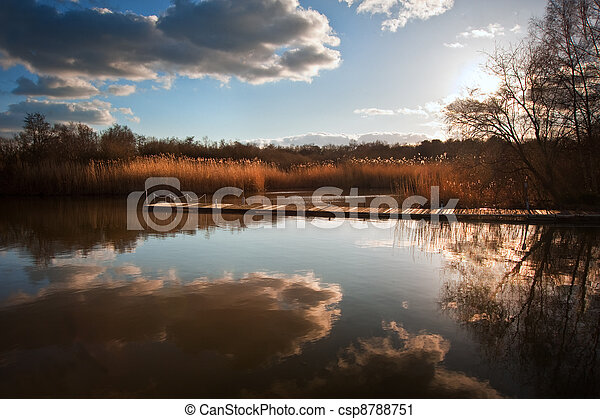 Beautiful image of sunset landscape of wooden fishing jetty on calm lake with clear reflections - csp8788751