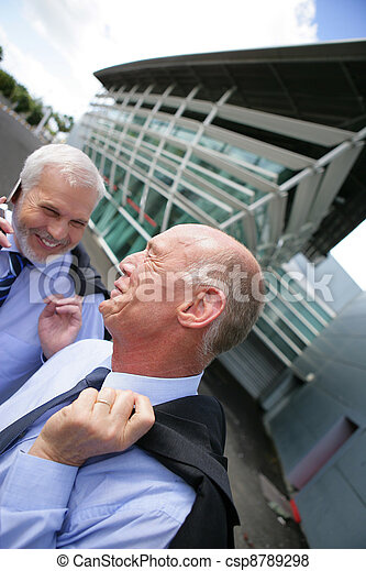 Businessmen laughing outside
