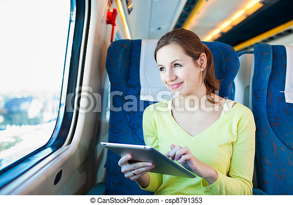 Young woman using her tablet computer while traveling by train  - csp8791353