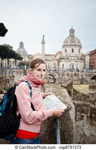 Pretty young female tourist studying a map at the Trajan's forum in Rome, Italy (dome of the Santissimo Nome di Maria church in the background) - csp8791373