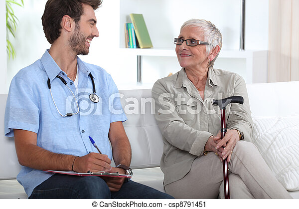 Senior woman talking to a young medic - csp8791451