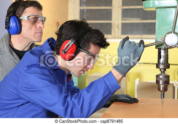 Young man using a bench drill - csp8791485