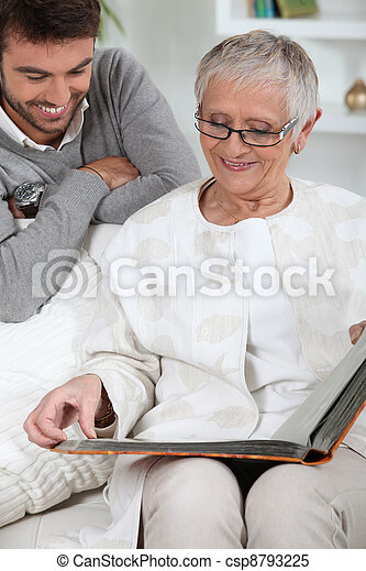 Elderly person looking at photos with son - csp8793225