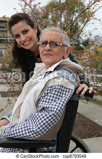 Young woman pushing an elderly lady in a wheelchair - csp8793549