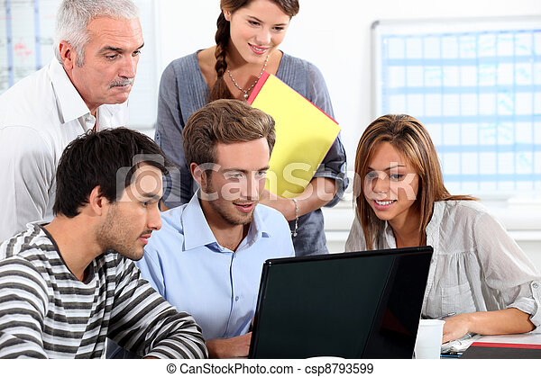 Informal team of people sitting round a laptop computer - csp8793599