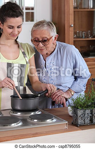Young woman cooking for an elderly lady - csp8795055