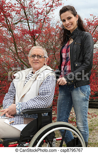 Young woman pushing an elderly lady in a wheelchair - csp8795767