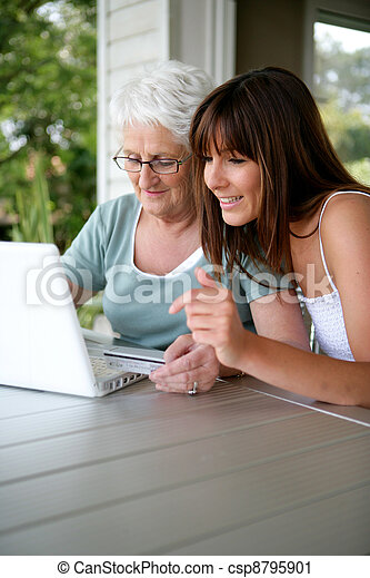 Mother and daughter using laptop - csp8795901