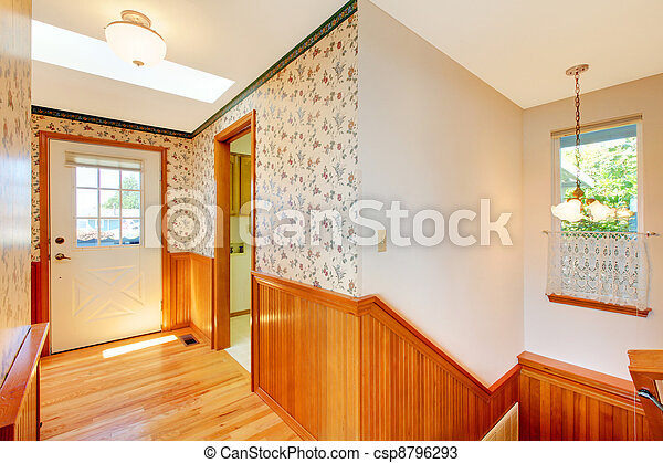 Sunny cozy hallway with staircase and front door and warm wood. - csp8796293