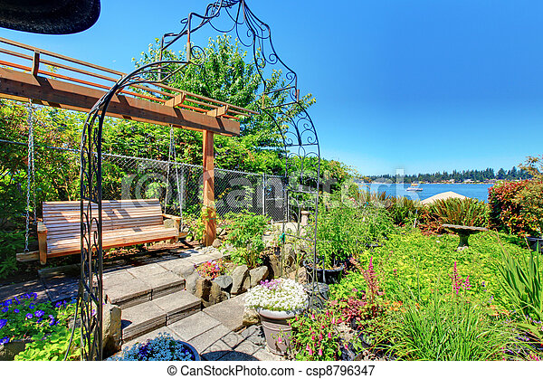 Private home Garden with a swinging bench near the lake. - csp8796347