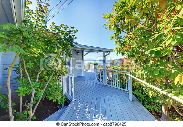 Grey House Exterior with deck walkway and water view. - csp8796425