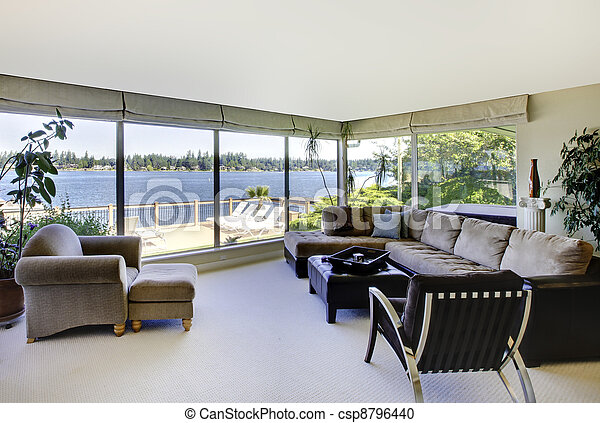 Living room with fireplace and water view with large windows. - csp8796440