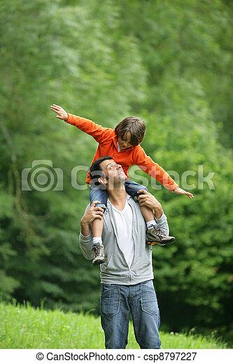 Little boy sat on father\'s shoulders