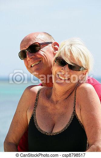 Senior couple stood on a secluded beach - csp8798517