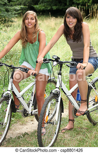 Two teenage girls riding bikes in countryside - csp8801426