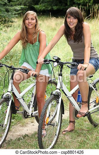 Two teenage girls riding bikes in countryside - csp8801426