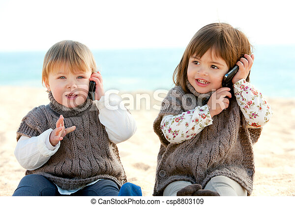 two babie girls talking on mobile phones. - csp8803109