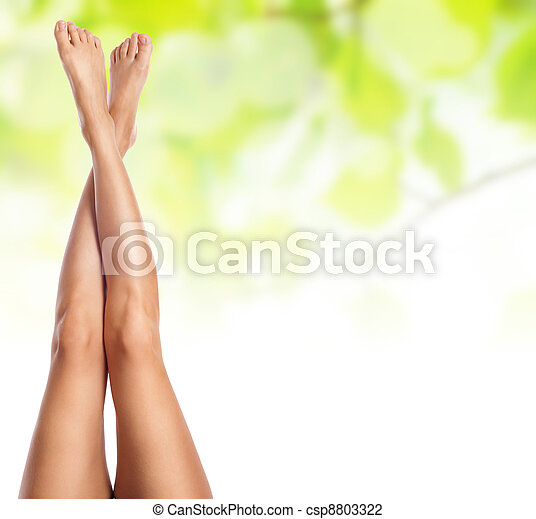 healthy sexy slender female legs over green natural spring background - spa and healthcare concept  - csp8803322