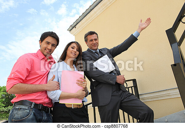 Couple with their realtor in front of their new house - csp8807768