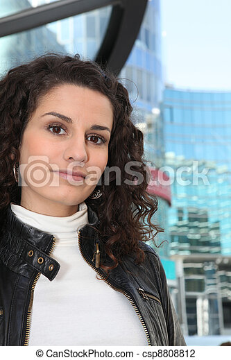 Uncertain woman standing in front of a modern building - csp8808812