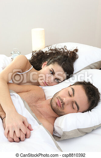a woman contemplating his man sleeping - csp8810392