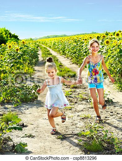 Kids running across sunflower field outdoor. - csp8813296