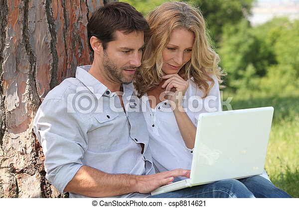 Couple in park on laptop - csp8814621