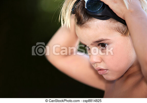 Young boy putting on swimming goggles - csp8814825