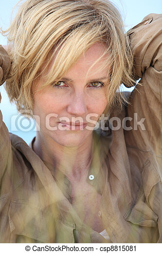 Closeup of woman with short blonde hair and arms behind her head - csp8815081