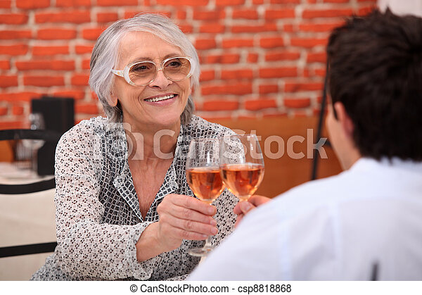 Older woman drinking rose wine in a restaurant with a young man - csp8818868