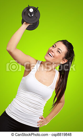 portrait of young girl training with weights over green background - csp8819848